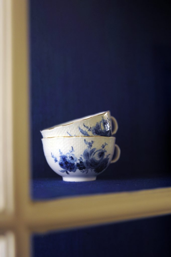 blue and white delft cups in a cupboard with blue background
