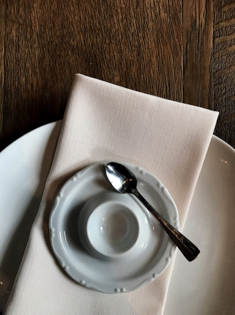 white egg cup and spoon on a peach linen napkin on a wooden table