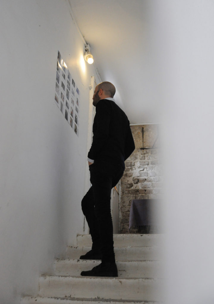man on stairs looking at exhibition on walls