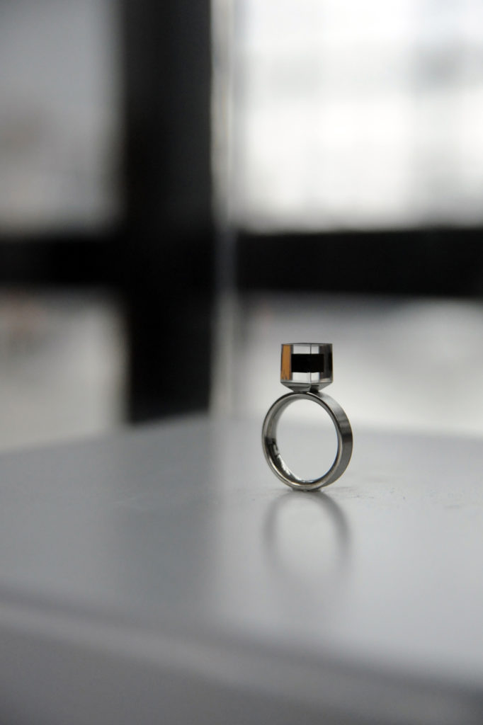 monotone picture of a ring with a square acrylic box of compressed carbon attached