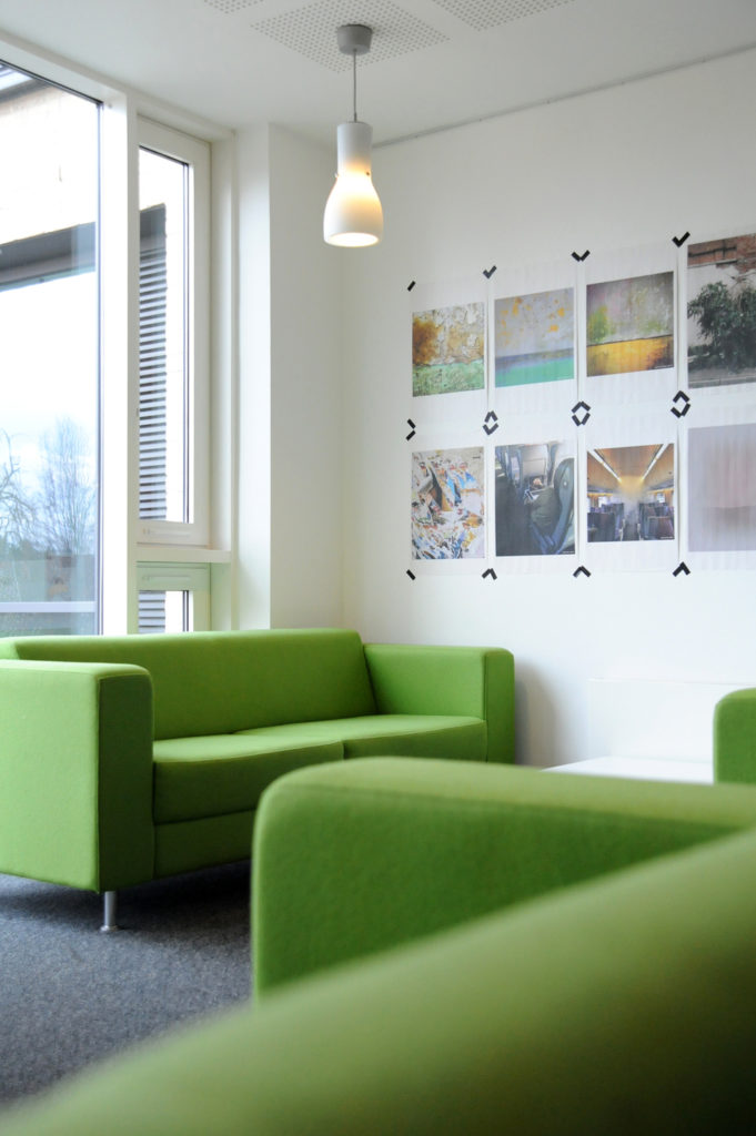 view of exhibition space with lots of prints taped to the wall