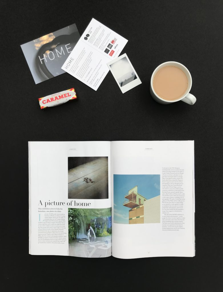 open magazine with article about exhibition called home on a table with cup of tea and a tunnocks caramel