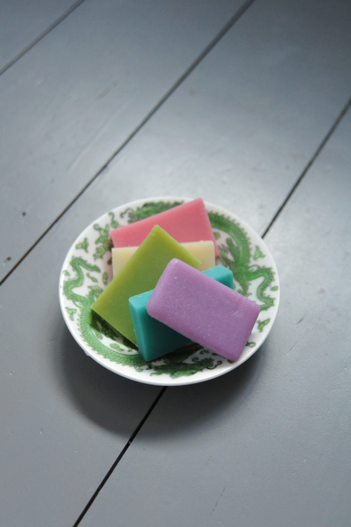different coloured bars of solid shower gel in a dish on a grey table