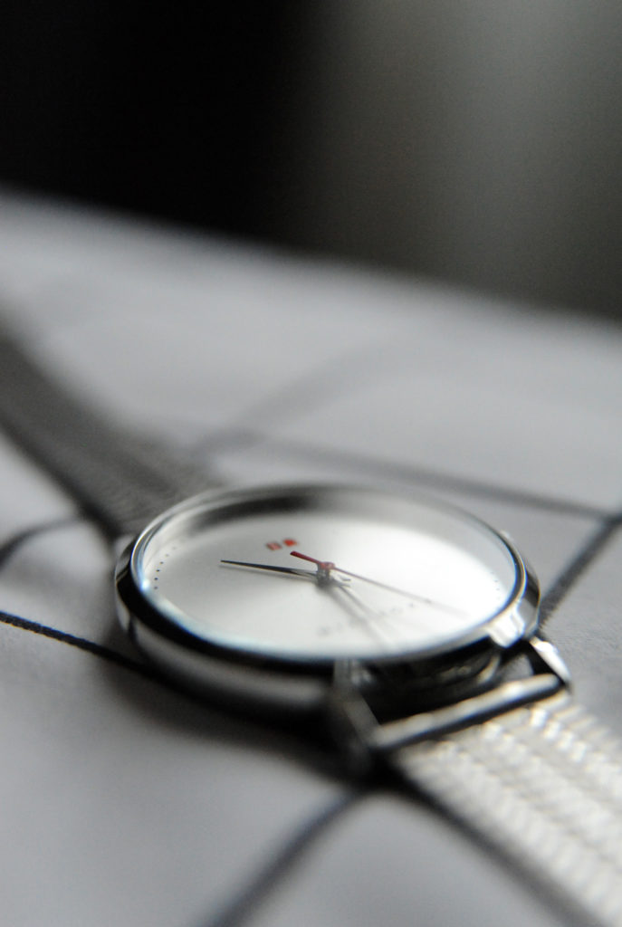 a silver toned watch on a white and black checked fabric background