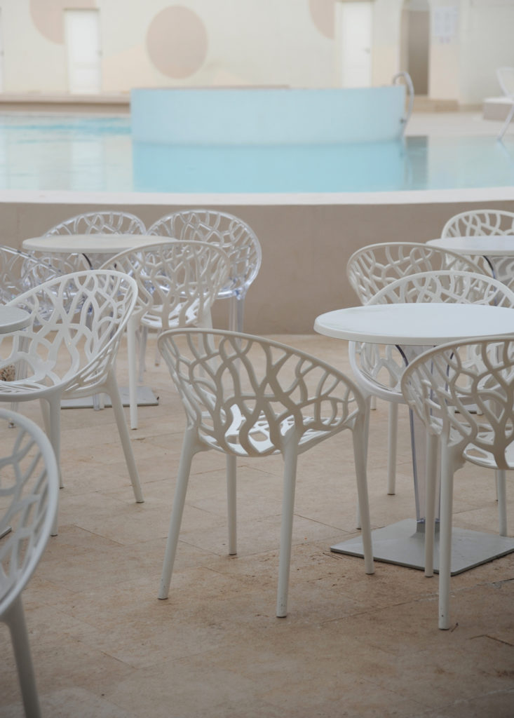 white chairs and tables beside a swimming pool
