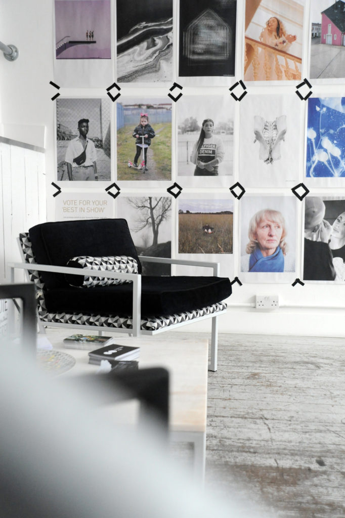 a room with a black arm chair and a white floor with multiple photographs taped to the wall in a grid formation