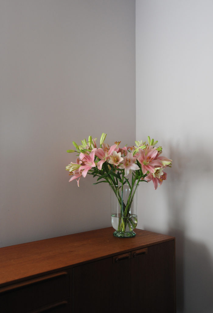 pink lilies in a glass vase on a wooden sideboard