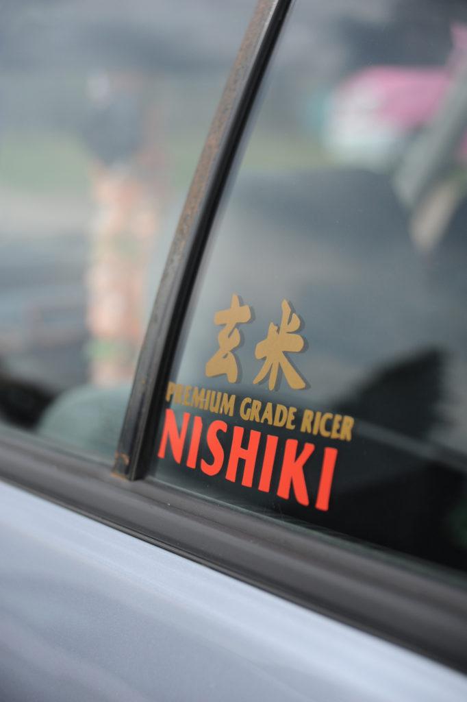 window sticker in Japanese car reading Premium Grade Rice Nishiki