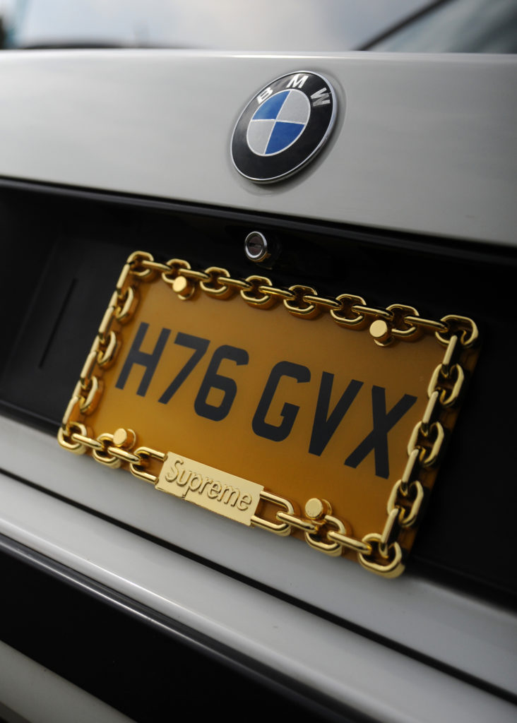 gold Supreme chain around a number plate on a white BMW car