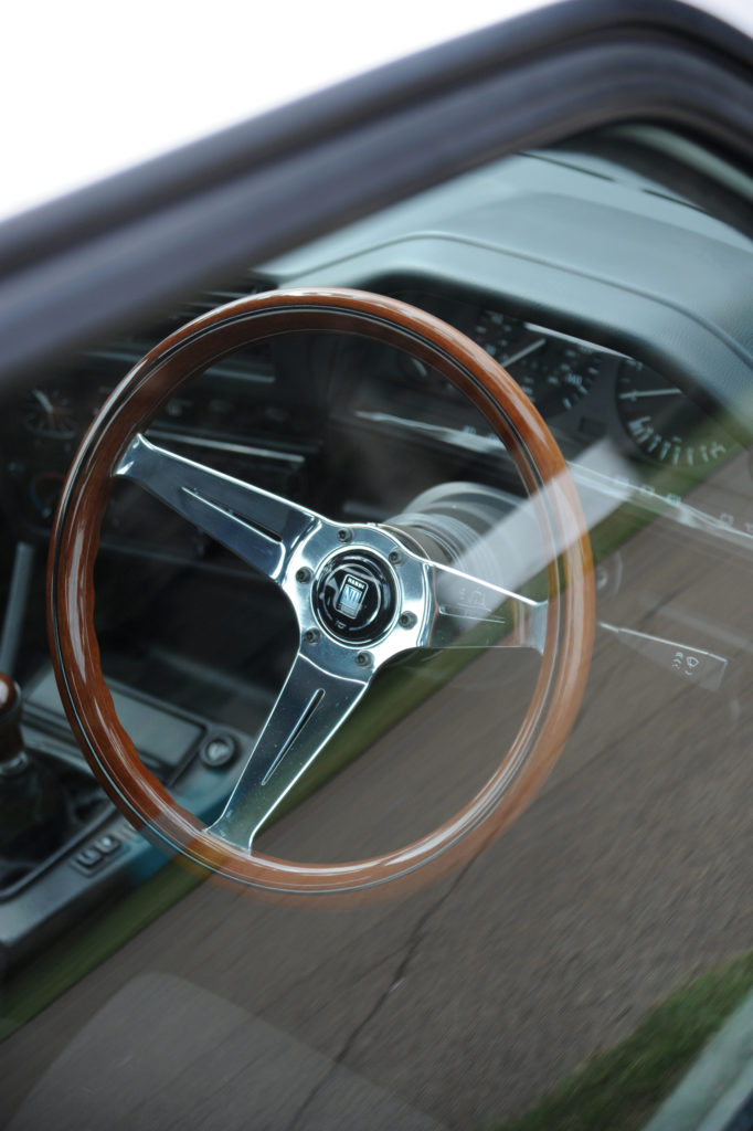 wooden steering wheel seen through car window