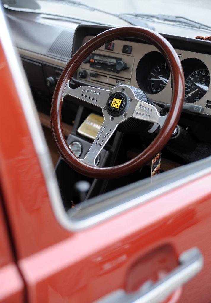 momo steering wheel through the window of custom painted canyon red volkswagen golf mk1