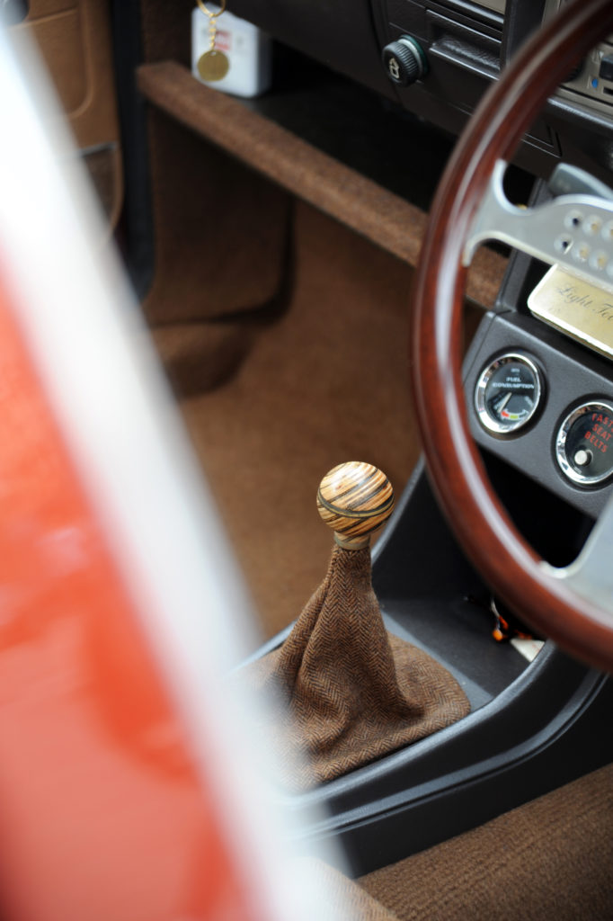 wooden gear knob wheel through the window of custom painted canyon red volkswagen golf mk1