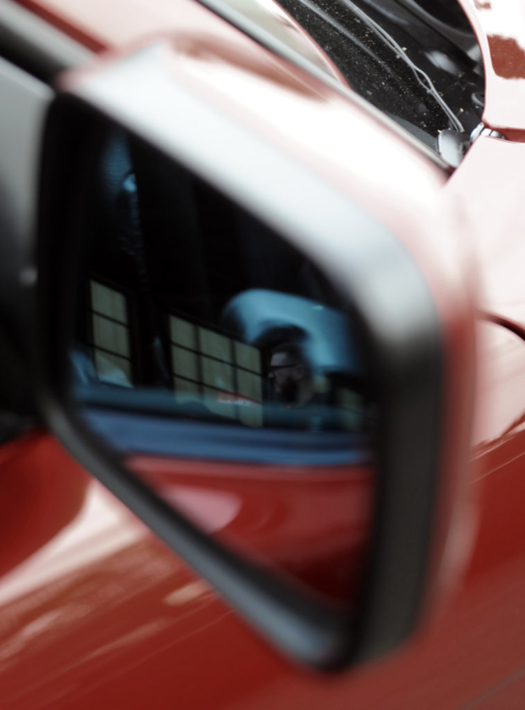 blurred reflection in wing mirror of red car